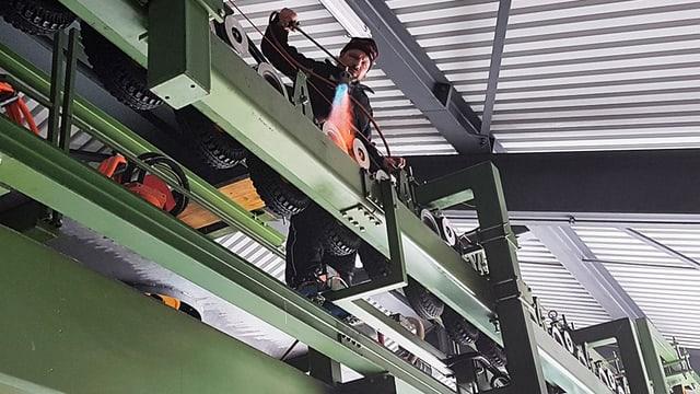 Mann klettert über Metallgerüst mit Tragseilen.
