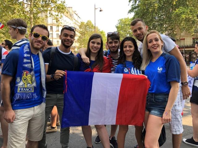 Fans halten eine Frankreich-Flagge in den Händen und posieren.