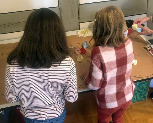 Zwei Mädchen von hinten, die an einem Pult stehen.