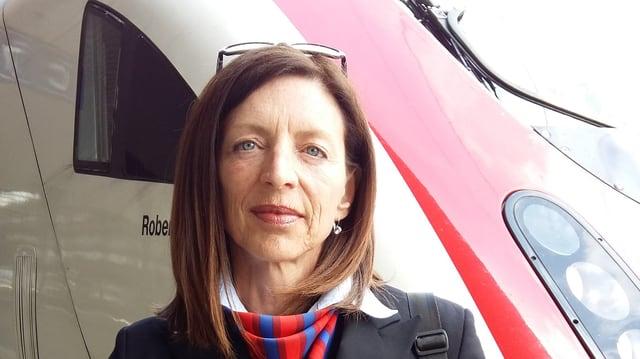 Thomasina Müller en mondura davant ina locomotiva.