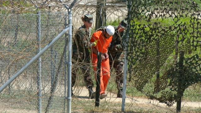 Ein gefesselter Gefangener in oranger Kleidung wird von zwei Soldaten - eines ist eine Frau - abgeführt; Aufnahme durch Gitter hindurch in Guantanamo.