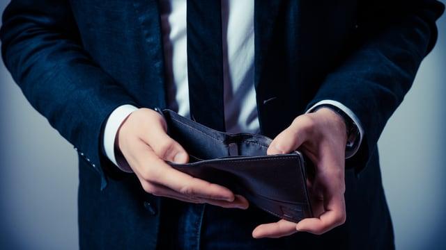 Mann zeigt seine leere Geldbörse
