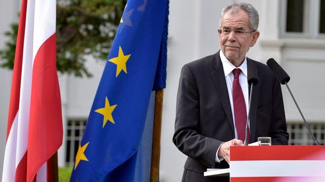 Van der bellen en ses discurs cun bandiera austriaca ed europeica.