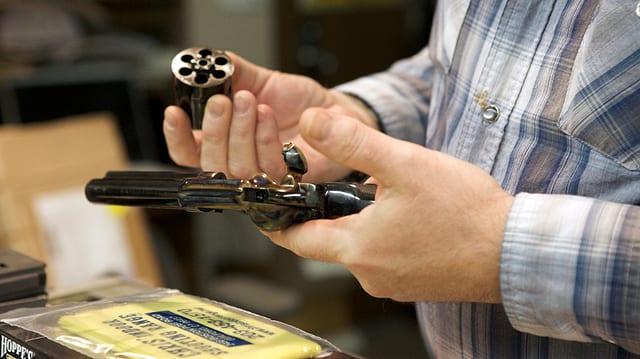 Ein Mann montiert einen Trommelrevolver.