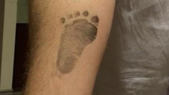 Chris O'Neill mit Babyfuss-Abdruck auf seinem Arm.