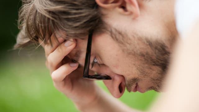 Ein Mann mit konzentriertem Blick stützt seinen Kopf in seiner Hand.