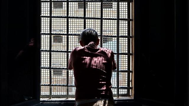 Ein Mann schaut durch ein vergitteretes Gefängnisfenster.