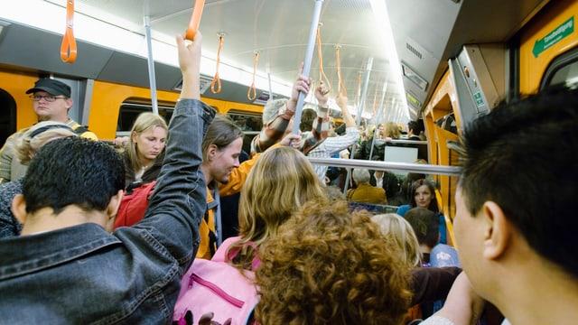 Stosszeit in einer S-Bahn, die Passagiere stehen eng gedrängt im Zug.