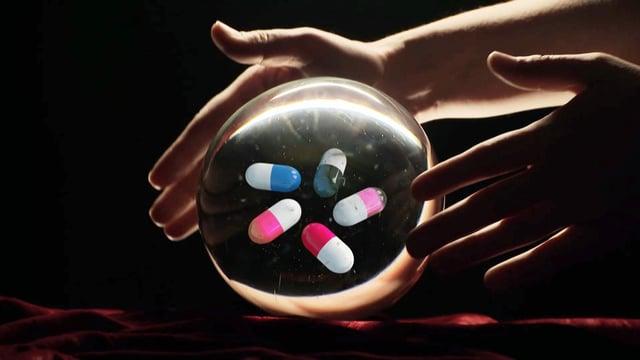 Glaskugel, darin vier bunte Pillen