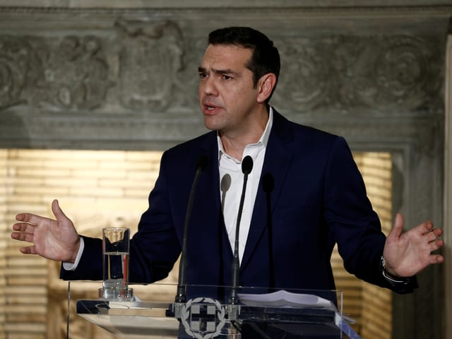 Tsipras steht am Rednerpult und signalisiert mit ausgestreckten Händen seine Offenheit.