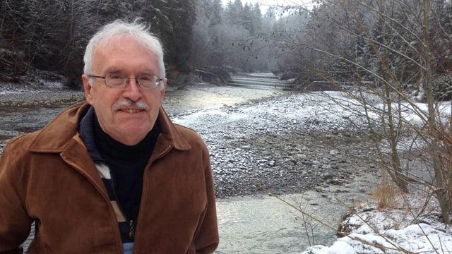 Mann steht an Fluss.