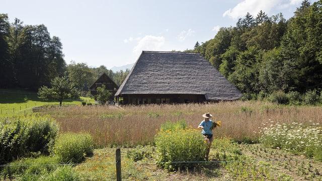 Ein Mann auf einem Feld vor einem traditionellen Haus.