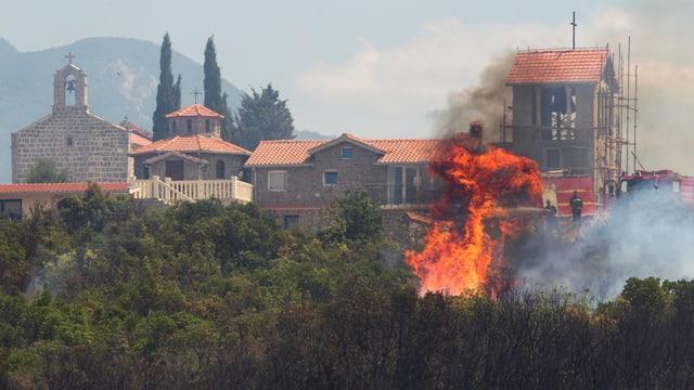 Feuer im Vordergrund, im Hintergrund ein Haus.