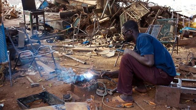 Ein Mann schweisst auf dem Boden ein Metallobjekt.