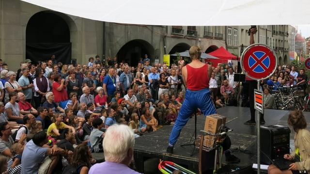 Ein Mann steht auf der Bühne, Kinder und Erwachsene schauen ihm sitzend und stehend zu.