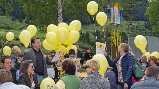 Menschen mit gelben Ballonen