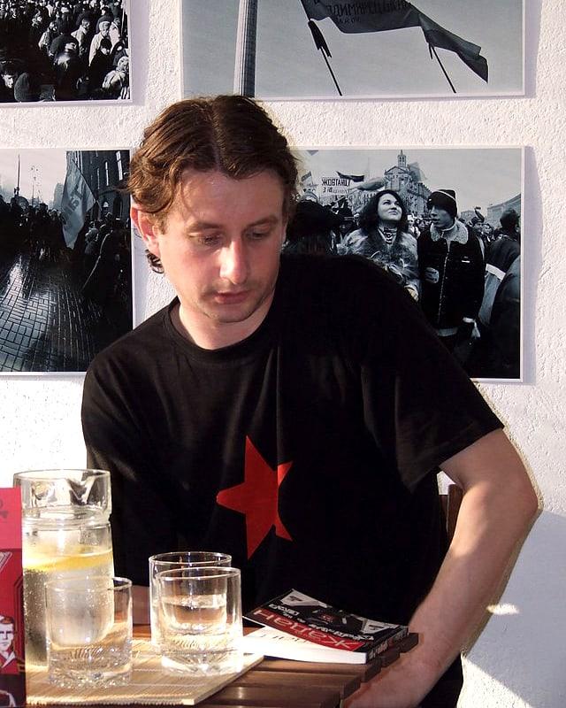 Ein Mann sitzt an einem Tisch, vor sich ein Buch, auf das er blickt. Er trägt ein schwarzes T-Shirt mit einem grossen roten Stern auf der Brust.