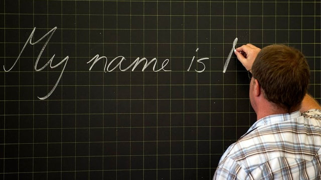 Lehrer schreibt auf die Wandtafel.