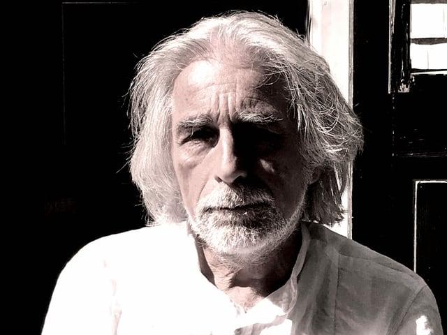 Schwarz-Weiss-porträt eines älteren Mannes mit langen weissen Haaren und einem weissen Hemd.