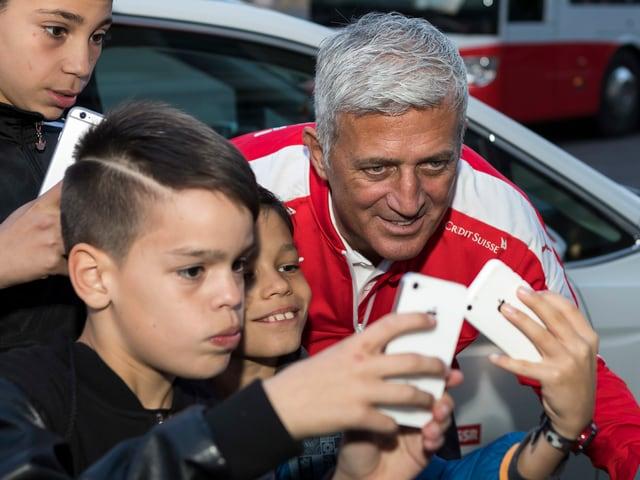 Vladimir Petkovic bückt sich für ein Selfie mit Kindern.