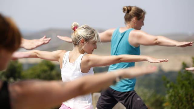 Drei Frauen praktizieren Yoga.