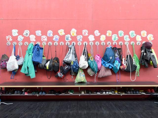 An einer Wand hängen Jacken und Taschen