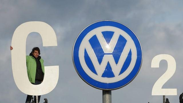 Ein Greenpeace-Mitarbeiter stellt den Buchstaben C vor dem VW-Logo.