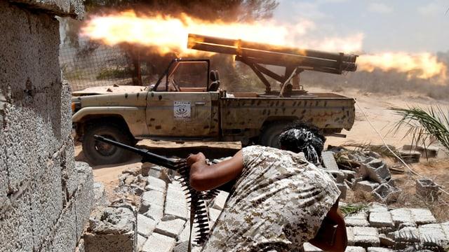 Mann mit Maschinengewehr vor Auto mit Raketenwerfer