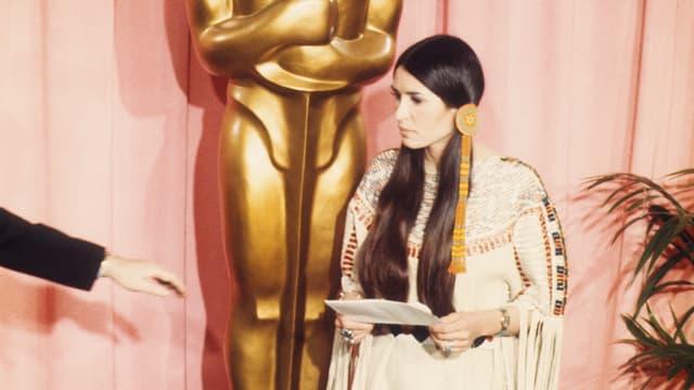 Aktivistin Sacheen Littlefeather steht in traditioneller indianischer Kleidung vor einer grossen Oscar-Statue.