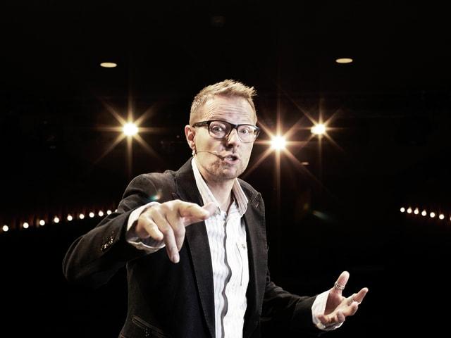 Ein Mann mit kurzen Haaren und Brille steht vor dunklem Hintergrund auf einer Bühne.