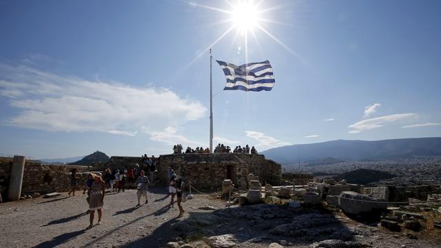 Touristen unter einer griechischen Flagge