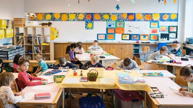 Eine Schulklasse, die Kinder sitzen an den Pulten und schreiben.