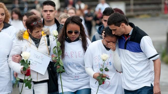 Menschen mit weissen Rosen. Eine Frau weint und wird getröstet.