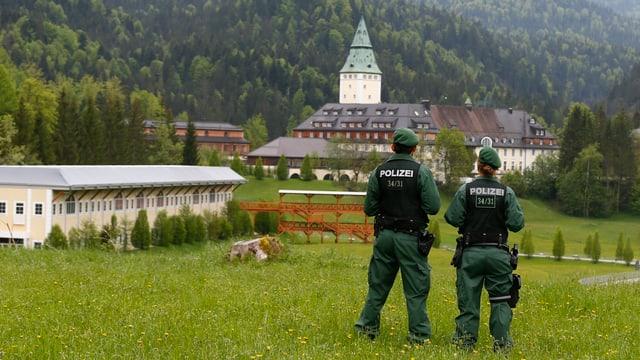 Polizisten blicken auf das Schloss Elmau.