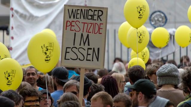 """Transparent """"Weniger Pestizide im Essen"""" und Menschenmenge."""