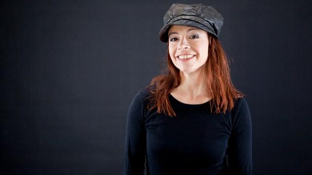 Frau mit langen rötlichen Haaren und Lederkappe.