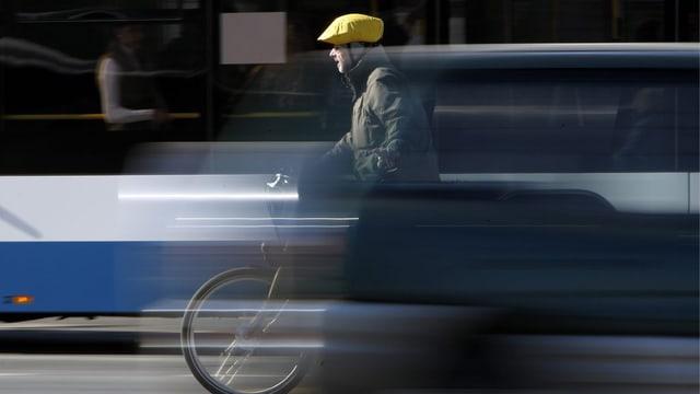 Ein Velofahrer mitten im Verkehr.