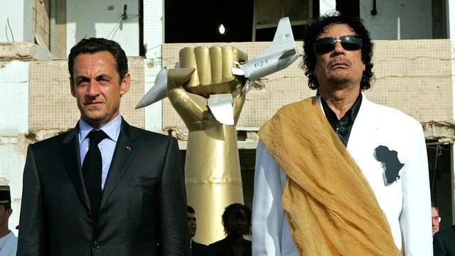Links steht Nicolas Sarkozy, rechts Gaddafi, in der Mitte eine goldene Hand, die ein amerikanisches Flugzeug zerquetscht.