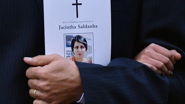Eine Hand hält ein Bild auf dem ein Kreuz und ein Frauenportät zu sehen ist.