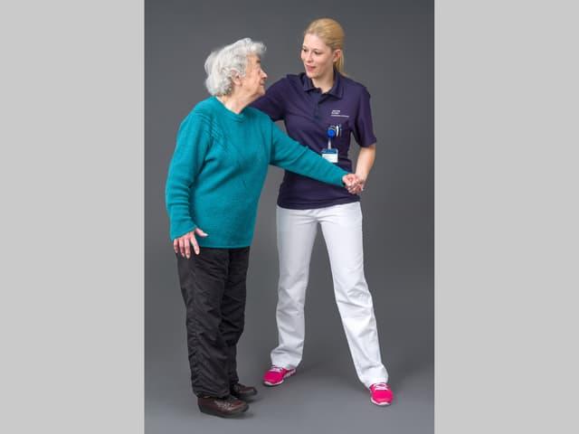 Seniorin steht auf den Fersen und wird dabei von einer jungen Frau gestützt