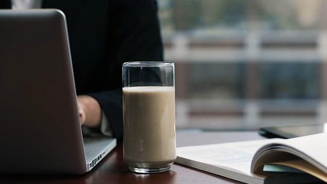 Ein Glas mit beiger, milchiger Flüssigkeit neben einem Computer und einem Buch.