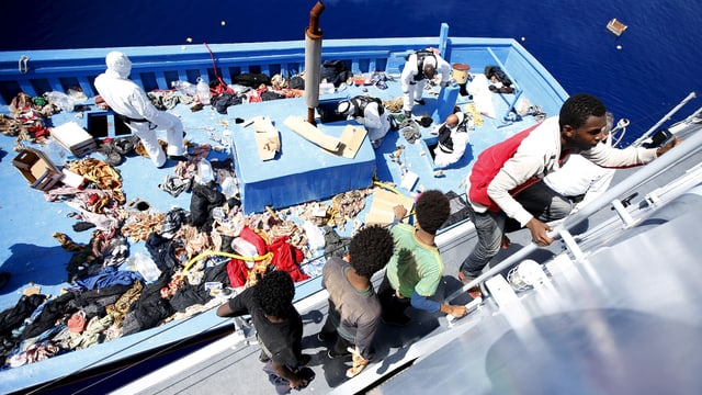 Flüchtlinge steigen die Leiter hoch. Das Deck des Flüchtlingsschiffs ist übersät mit Kleider und Abfällen.