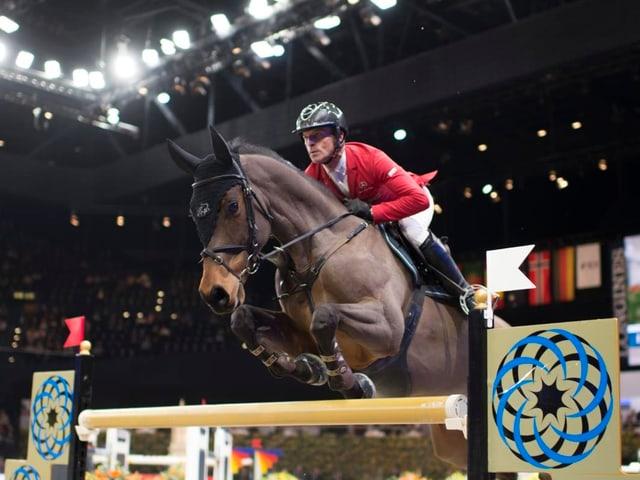 Ein Reiter springt mit auf einem Pferd über ein Hindernis.