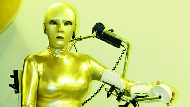 Eine Frau in roboterhaftem Goldkostüm.