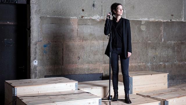 Ariane von Graffenried steht mit einem Mirophon auf einer leeren Bühne aus Paletten.