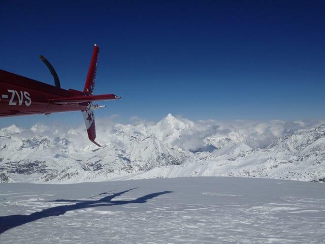 Aufnahme mit Helikopter-Heck und Gebirgs-Hintergrund.