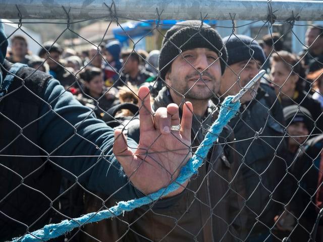 Ein Mann steht hinter einem Zaun.
