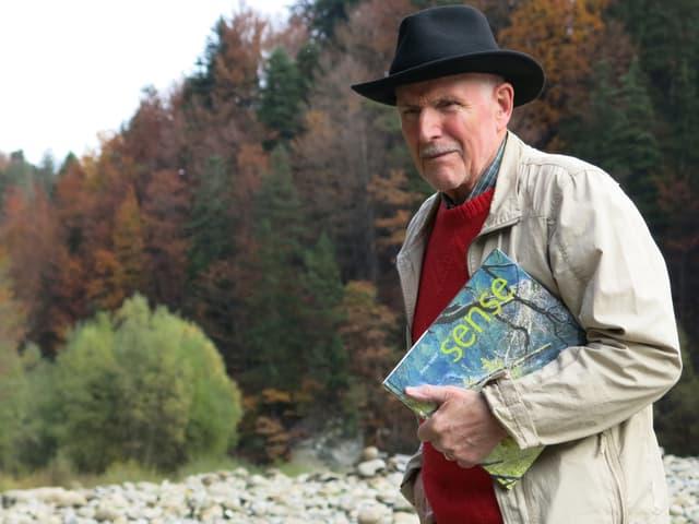 Der Mann mit Hut steht an der Sense mit einem Buch unter dem Arm.