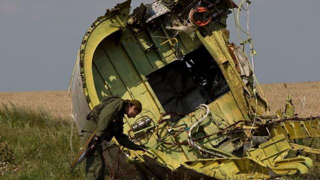 Separatist vor einem Teil des Rumpfs der abgstürzten Maschine