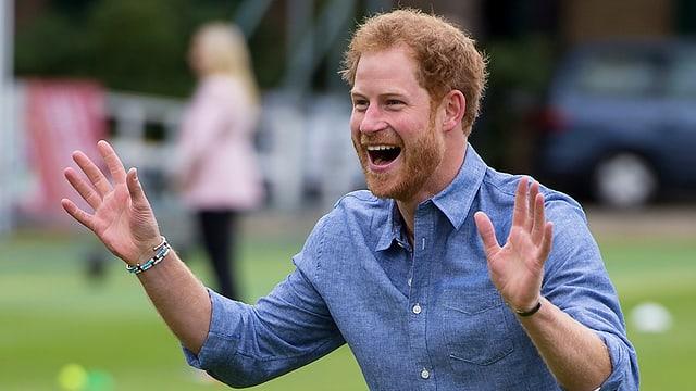 Prinz Harry steht mit ausgestreckten Armen da und trägt am rechten Handgelenk ein hellblau-weisses Armband